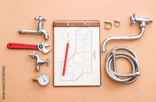 Fotografía Set of plumbing items with house plan on color background