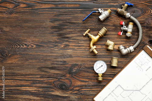 Fotomural  Set of plumbing items with house plan on wooden background