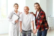 Young Man Visiting His Elderly Father In Modern Clinic