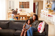 Mother And Daughter Sitting On Sofa At Home Watching Movie On TV Together
