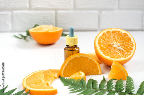 Fototapeta Vitamin C and Mesotherapy. Serum with vitamin C in brown glass bottles, leaf fern and orange in a cut. High dose vitamin c synthetic for skin. Organic Natural Cosmetics Concept obraz