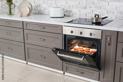 Open oven with tasty homemade cookies in kitchen Canvas Print