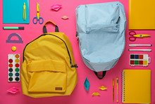 School Backpacks And Stationery On Color Background