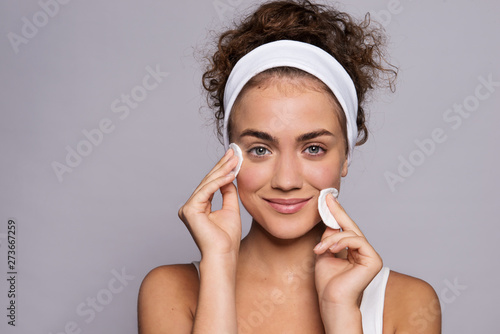 Valokuva Portrait of a young woman cleaning face in a studio, beauty and skin care