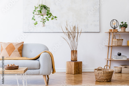 Fototapeta The stylish boho compostion at living room interior with design gray sofa, wooden coffee table, bamboo shelf and elegant personal accessories. Honey yellow pillow and plaid. Cozy apartment. Home decor obraz