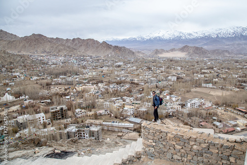 Foto op Canvas Schapen Traveler man standing on Leh Ladakh city view from Shanti Stupa. Beautiful amazing village in the valley with snow mountain at background. Ladakh, India.