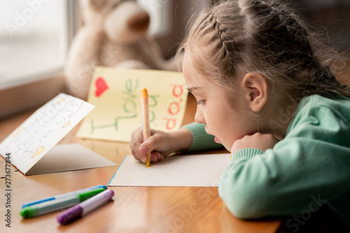 Obraz Concentrated girl making postcard for daddy - fototapety do salonu
