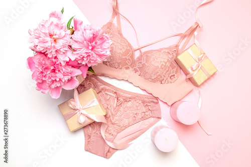 Fotografía  Female elegant pink lace bra and panties, flowers pink candles, a bouquet of bea
