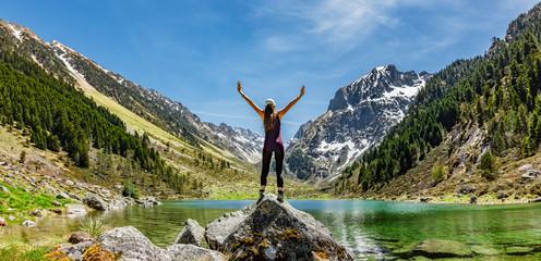 Frau in Siegerpose auf einem Felsen an einem See in den Bergen