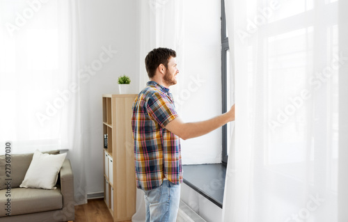 Kiev people concept - young man opening window curtain at home