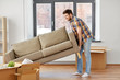 moving, people and real estate concept - happy man dragging sofa at new home