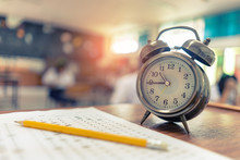 Test Examination In Education Concept,pencil And Alarm Clock On Wooden Table,students Exams In A Classroom Background ,Scholarship Tests For Study Abroad