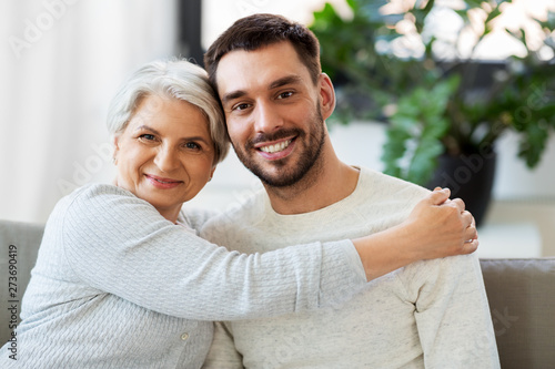 Fototapeta family, generation and people concept - happy smiling senior mother with adult son hugging at home obraz