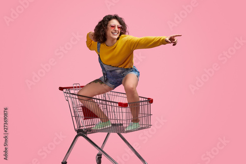Fotografia Cheerful young woman riding forward on shopping cart
