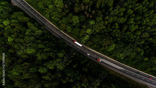 Aerial view flying over road, that lead through the green forest. Fototapete
