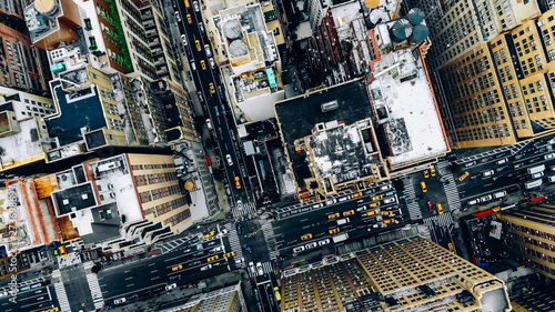 Aerial view of New York downtown building roofs. Bird's eye view from helicopter of cityscape metropolis infrastructure, traffic cars, yellow cabs moving on city streets and crossing district avenues