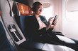 Young caucasian woman sitting near window with smartphone connected to wifi internet during flight on board, female passenger in headphones for noise cancellation search songs in online shop on app