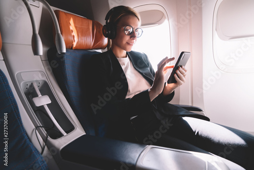 Valokuva  Young caucasian woman sitting near window with smartphone connected to wifi inte