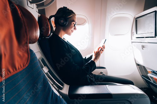 Side view of woman in formal wear watching online positive video while using wireless internet connection on board, female passenger reading news while listening audio record via headphones - 273700675