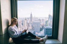 Trendy Dressed Hipster Girl Using Digital Tablet While Sitting On Hotel Window Sill With Breathtaking Scenery View Of New York Cityscape. Female Digital Nomad Working Remote On Freelance, Millennials