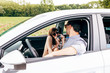 couple in a car having fung on plying with a old fashioned photo camera. love, summer, holiday, travel, relax, joy, togetherness concept