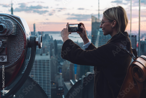 Fotografie, Tablou  Caucasian young woman traveler making video on cellphone camera while standing on open Observation Deck with scenery view New York cityscape at sunset