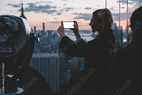 Female tourist preparing her smartphone camera for make photo of scenery New York view from open Observation deck Tablou Canvas