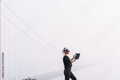 Valokuva  Female trying virtual reality experience while standing near copy space with bridge construction on background