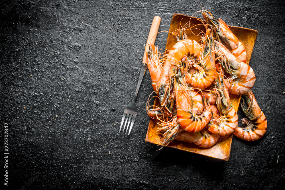 Fototapety, obrazy: Cooked shrimps on a wooden plate with a fork.