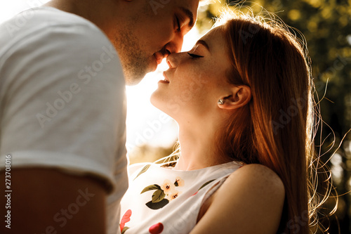Carta da parati  Side view portrait of a amazing red haired woman with freckles kissing with her boyfriend against sunset while dating in their vacation time