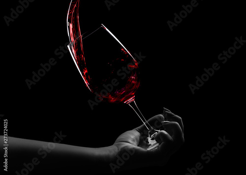 Fotografija  a glass of wine in hand, red wine pours into a glass, an over black background