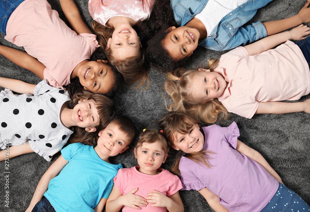 Fototapety, obrazy: Adorable little children lying on floor together indoors, top view. Kindergarten playtime activities