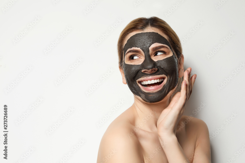 Fototapeta Beautiful woman with black mask on face against light background. Space for text