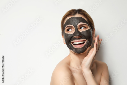 fototapeta na drzwi i meble Beautiful woman with black mask on face against light background. Space for text