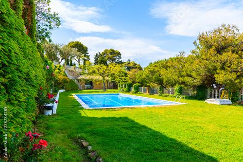 Foto auf Leinwand Texturen TOSSA DE MAR, SPAIN - JUN 3, 2019: Swimming pool in garden of luxury house in Tossa de Mar town, Costa Brava, Spain.