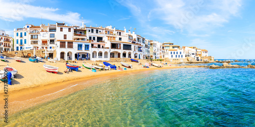 Foto  CALELLA DE PALAFRUGELL, SPAIN - JUN 6, 2019: Panorama of amazing beach in scenic fishing village with white houses and sandy beach with clear blue water, Costa Brava, Catalonia, Spain