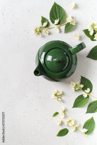 Jasmine tea with teapot, flowers and leaves on white background