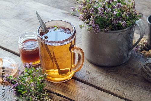 Fotografie, Obraz Mug of thyme healthy herbal tea, honey jar and rustic metal cup full of thymus serpyllum medicinal herbs