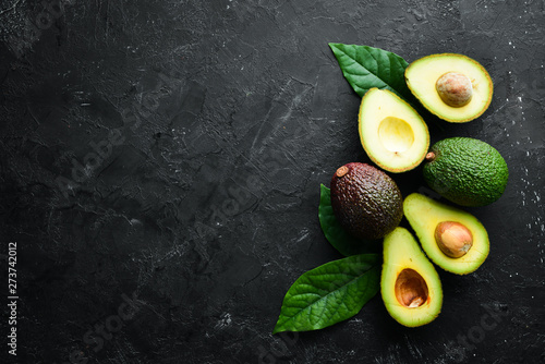 Obraz na plátne Fresh avocado with leaves on a black background