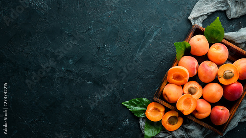 Fotografia, Obraz Fresh apricots with green leaves in a box