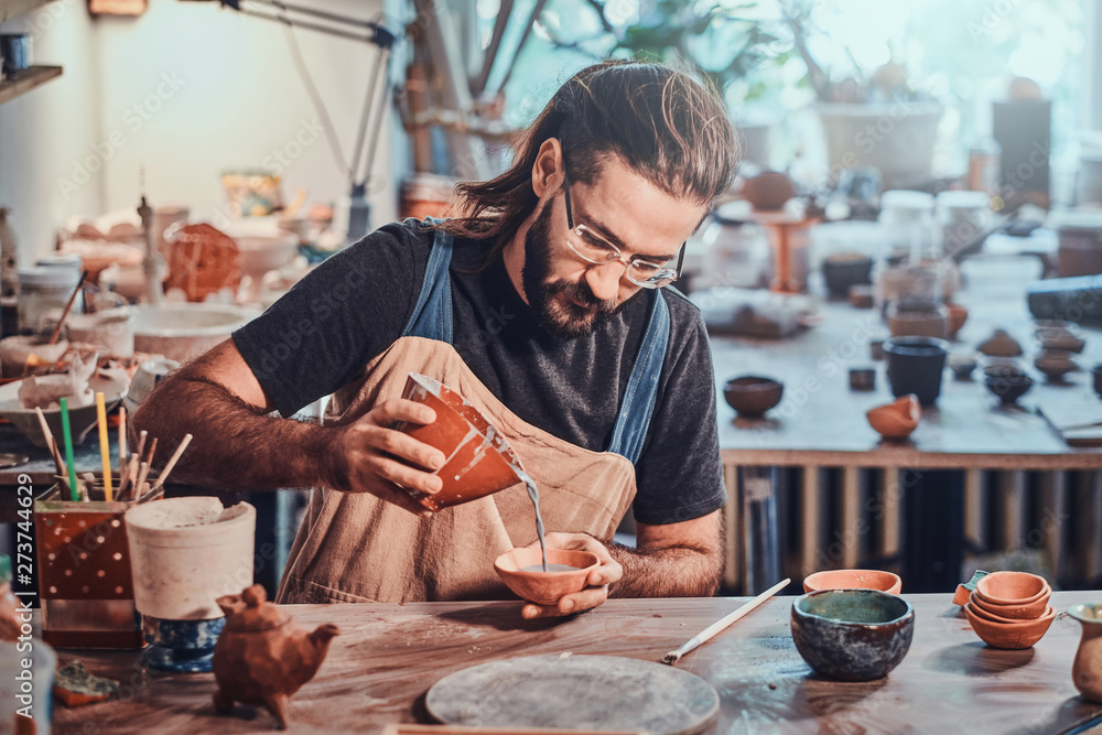 Fototapeta Diligent man is putting colourful clay to his new handmade pot.