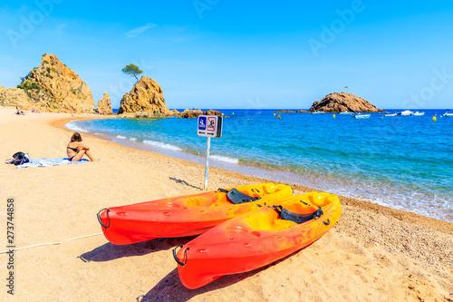 Foto auf Gartenposter Orange Colorful kayaks on beautiful beach in Tossa de Mar town, Costa Brava, Spain