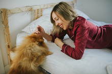 Young Happy Smiling Attractive Woman In Pajamas Lying In Bed With Little Fluffy Dog