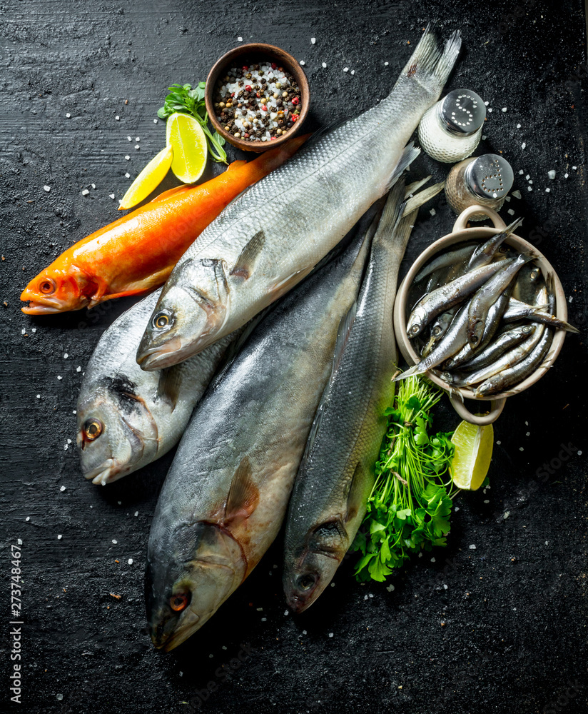 Fototapeta Assortment of fresh fish with spices, herbs and chopped lime.
