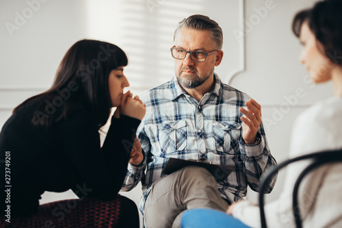 Foto  Arabic woman listening to her psychotherapist during support group for abuse sur