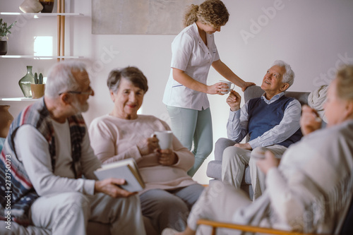 Kiev Senior man taking a cup of tea from his caregiver in the nursing home