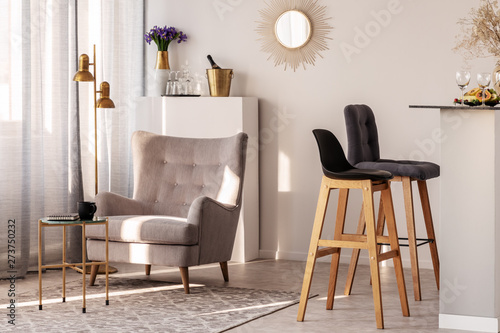 Awe Inspiring Trendy Grey Armchair Next To Two Black Wooden Bar Stools In Pabps2019 Chair Design Images Pabps2019Com