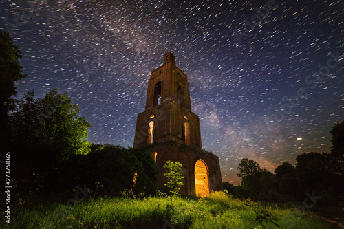 night bell tower ruin in forest at starry night with internal light