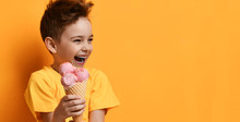 Baby Boy Kid Hold Strawberry Pink Ice-cream In Waffle Cone Happy Laughing Looking At The Corner On Yellow