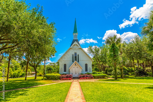 Photo sur Toile Lieu de culte A small white Methodist church down a brick walk under blue skies